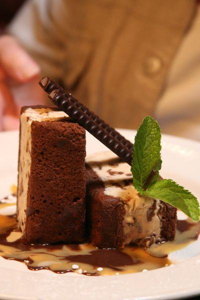 Chocolate peanut butter ice cream sandwhich served between chocolate fudge brownie cake