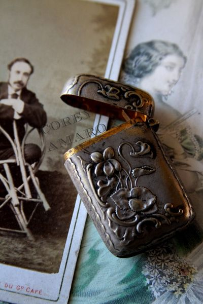 Silver match box, and man leaning on a chair