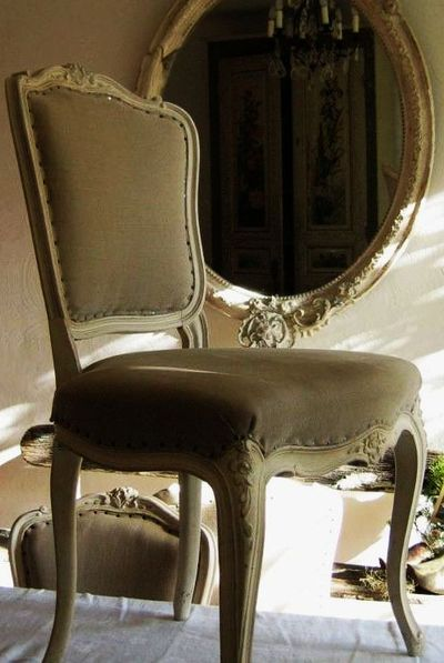 An antique chairs sits on the table looking at itself in the mirror